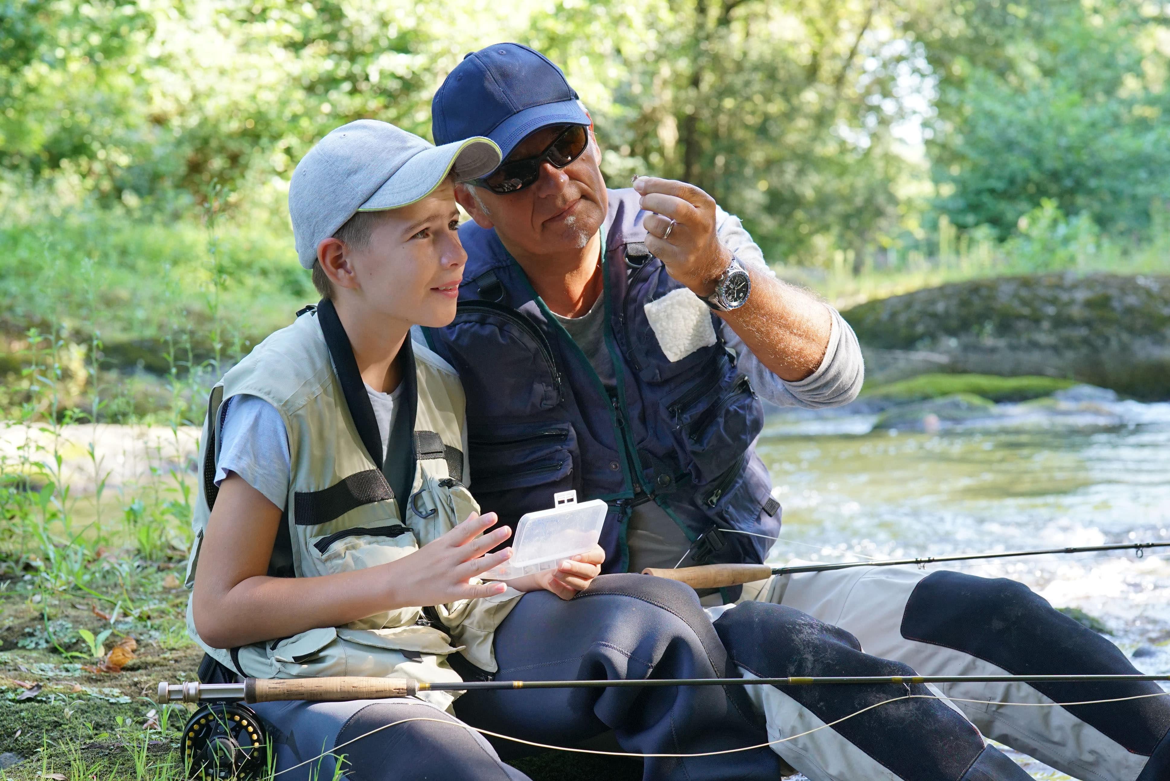 jeune garçon et son grand-père en train de discuter assis au bord de l'au avec leur canne à pêche
